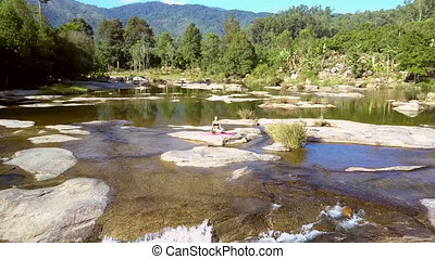 pictorial picture shallow river with rapids among jungle -...