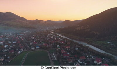 pictorial town buildings against hills hiding setting sun -...