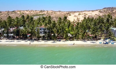 pictorial view sand beach lined by palms at hills -...