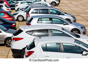 rows of cars standing on a parking lot