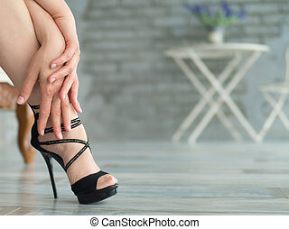Picture a pair of elegant slender female legs in beautiful shoes on high heels