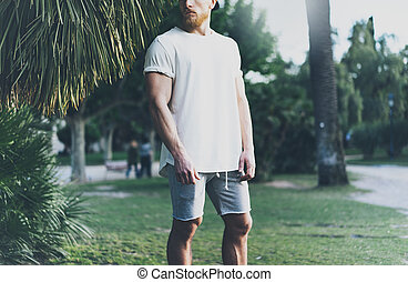 Picture Bearded Muscular Man Wearing White Blank t-shirt in summer time. Green City Garden.Relaxing time after hard work day. Blurred Background.Front view.Horizontal Mockup.