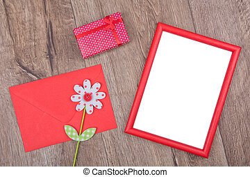 Picture frame and darling, envelope and flower on a wooden background