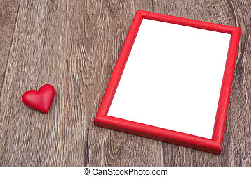Picture frame and heart on a wooden background