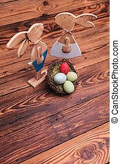 picture from above of wooden easter bunnies near egg basket