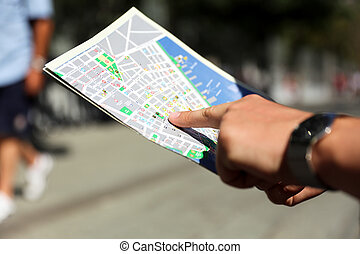 picture of a close up man is looking for directions on the map outside