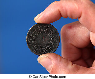 Fingers hold old coin from Ottoman empire