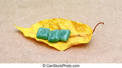 Green mints candy on an autumn leaf