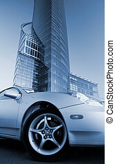 Picture of a modern sport car in front of office building (toned in blue)