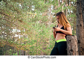 Sexy Blonde Girl writing sms after training in a park