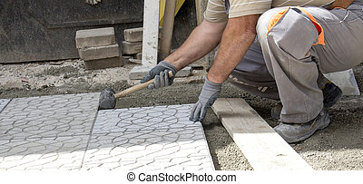 Worker tapping pavers into place with rubber mallet. -...