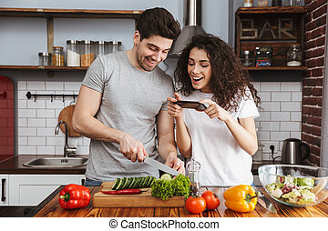 Picture of adorable couple man and woman 30s cooking salat with vegetables together in modern kitchen at home