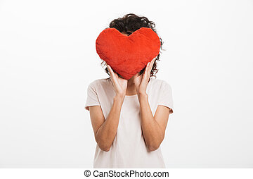 Picture of amusing woman 20s with brown hair covering face with red heart shape pillow, isolated over white background