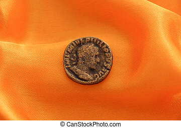 picture of an Old coin on yellow fabric