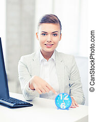 attractive businesswoman pointing at clock