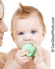 baby boy with green plastic toy - picture of baby boy with...