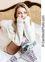 picture of beautiful blond young woman blue eyes girl in knitted looking at camera happy smiling on white bed background