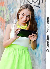 picture of beautiful stylish fashion blond young woman reading message on tablet pc computer having fun happy smiling using internet at graffiti wall on city urban summer or spring outdoors background