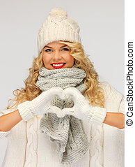 beautiful woman in a winter clothes showing heart