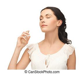 woman spraying perfume on her neck