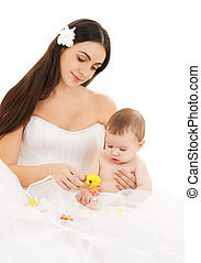 bride in white dress with little baby