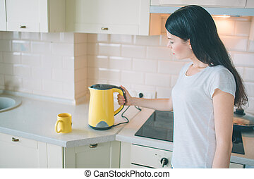 Picture of brunette stands and looks on kettle. She turns it on. Woman holds hand on the side of kettle. She is in kitchen.