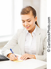 businesswoman writing on sticky note - picture of...