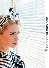 picture of closeup on beautiful blond young woman pinup girl having fun ... happy smiling & looking  thoughtfully through sun lighted windows