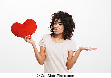 Picture of displeased american woman 20s with brown hair holding red heart shape pillow and expressing sadness, isolated over white background
