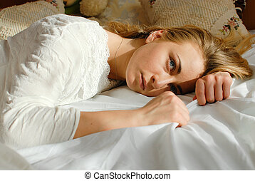 picture of emotional beautiful blond young woman relaxing lying in bed looking at copy space on bedroom background closeup portrait