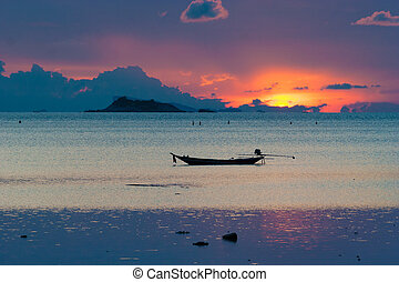 Picture of empty long tail boat on tropical beach at sunset....