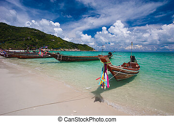 Picture of empty long tail boat on tropical beach. Clear...