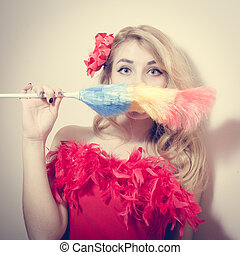 picture of gorgeous funny young blond pinup girl having fun holding dust sweeping brush and looking back at camera on white or light copy space background portrait closeup