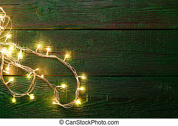 Picture of green wooden table with burning garland on side