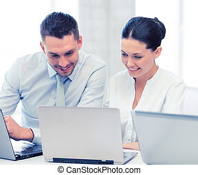 group of people working with laptops in office