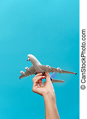 Picture of hand with airplane on empty blue background in studio.