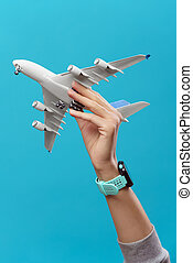 Picture of hand with airplane on empty blue background