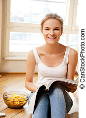 happy and smiling teenage girl with magazine