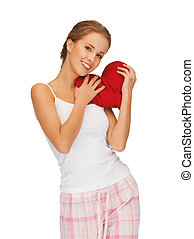 happy and smiling woman with heart-shaped pillow