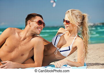 happy couple in sunglasses on the beach