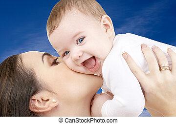 happy mother with baby boy over blue sky