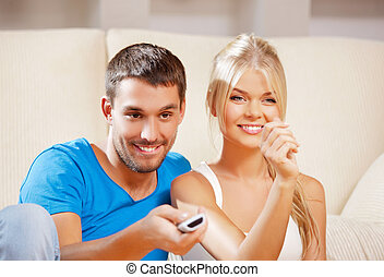 happy romantic couple with TV remote