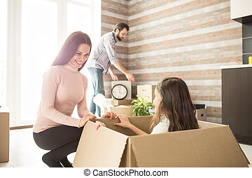 Picture of hard-working people. Man is putting a box of pans on the small table. His wife is sitting on her knees near her daughter an looking at her with a smile. Small girl is looking at her mother.