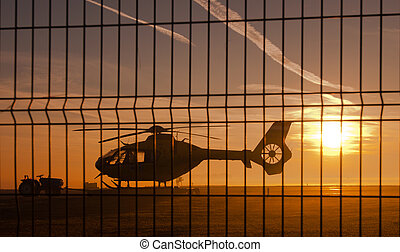 Picture of helicopter at sunset behind fence