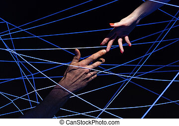 Picture of male and female hand among threads in ultraviolet