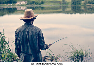 picture of man in straw hat having good time & fun fishing on river bank on peaceful summer day & water outdoors copy space background portrait