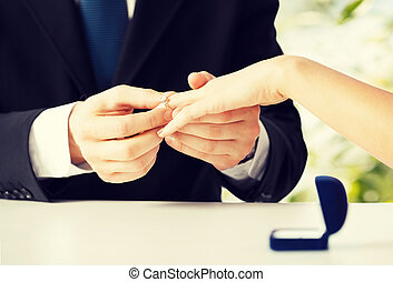 man putting wedding ring on woman hand - picture of man...