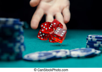 Picture of man throwing red dice on table with chips in casino