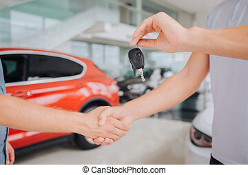 Picture of men shaking eah other's hands. Guy on right hold key in left hand. They stands in front of red car and besides white one.