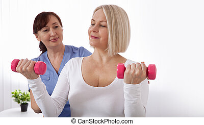 Picture of middle aged woman during rehabilitation in professional clinic. Rehabilitation, physiotherapy with dumbbells